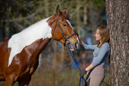 deportista chica y su caballo después de un montar a caballo en la primavera