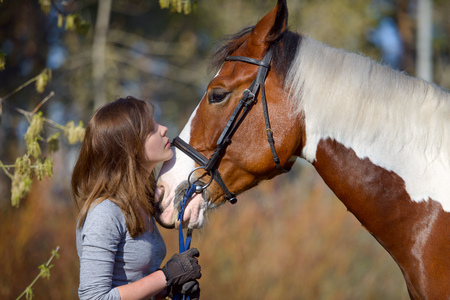 Girl sportswoman and her horse after a riding in the spring 版權商用圖片