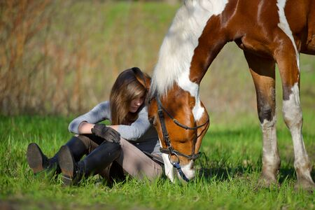 Girl sportswoman and her horse after a riding in the spring Stock Photo