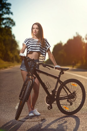 young girl posing standing with the bike on the road in the sunset time