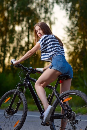 a young girl rides a Bicycle on the road outside the city in the sunset time