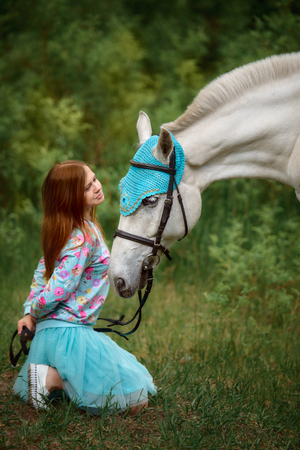 Love and understanding between man and animal. Redhead girl and white horse in the forest