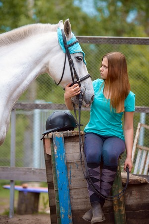 Meisje ruiter en haar paard om te rusten bij de stal na het rijden. Liefde en begrip tussen mens en dier.