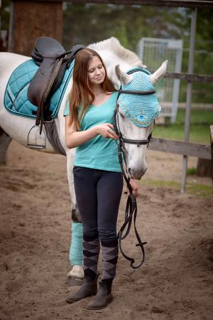 女の子ライダーと残りの部分に彼女の馬、乗馬後安定を近きます。愛と人間と動物間の理解。