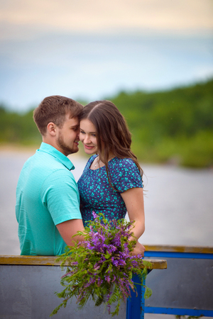Beautiful couple in love on the old bridge on sunset sky background. The love of a young couple men and women.