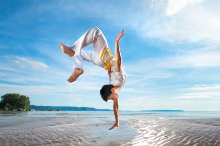 Ein junger Mann trainiert Capoeira am Strand - Konzept über Menschen, Lebensstil und Sport.