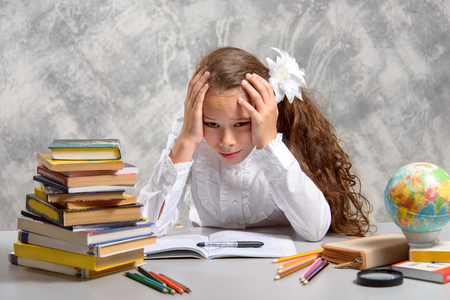 The schoolgirl in school uniform sits at the desk and thinks hard about the decision of the difficult task on a light gray background. Back to school. The new school year. Child education concept.