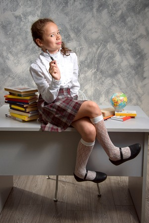 The fidget schoolgirl in school uniform sits on table and smiles happily on a light gray background. Back to school. The new school year. Child education concept.