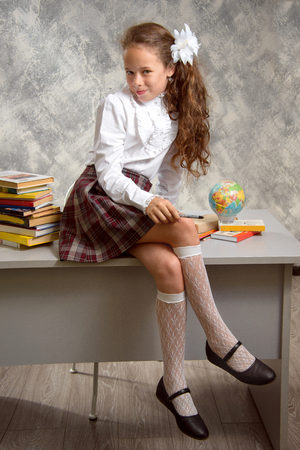 The fidget schoolgirl in school uniform sits on table and smiles happily on a light gray background. Back to school. The new school year. Child education concept. Фото со стока - 103862121