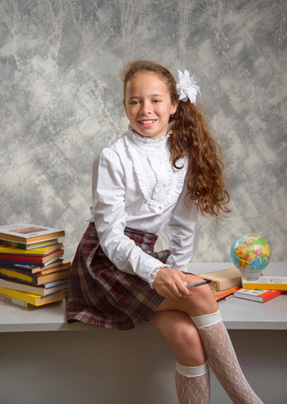 The fidget schoolgirl in school uniform sits on table and smiles happily on a light gray background. Back to school. The new school year. Child education concept. Banque d'images - 103862124