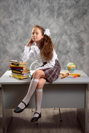Het onrustige schoolmeisje in schooluniform zit op tafel en lacht vrolijk op een lichtgrijze achtergrond. Terug naar school. Het nieuwe schooljaar. Kinderopvoeding concept.