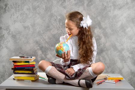 Das zappelige Schulmädchen in Schuluniform sitzt auf dem Tisch und lächelt glücklich auf einem hellgrauen Hintergrund. Zurück zur Schule. Das neue Schuljahr. Kindererziehungskonzept.