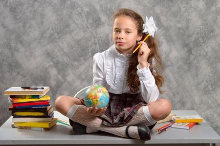 Het onrustige schoolmeisje in schooluniform zit op tafel en lacht vrolijk op een lichtgrijze achtergrond. Terug naar school. Het nieuwe schooljaar. Kinderopvoeding concept. Stockfoto