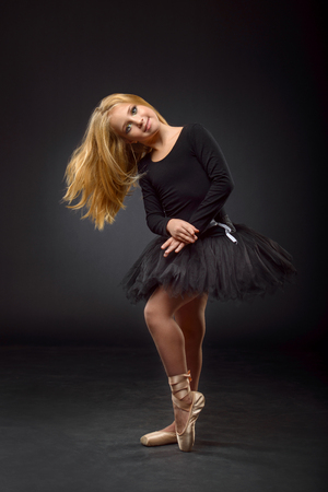 Cute little ballerina with long hair in a black tutu and pointe posing on a black background. The concept of children's creativity, development and sports.