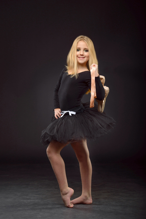 Cute little ballerina with long hair in a black tutu and pointe posing on a black background. The concept of childrens creativity, development and sports.