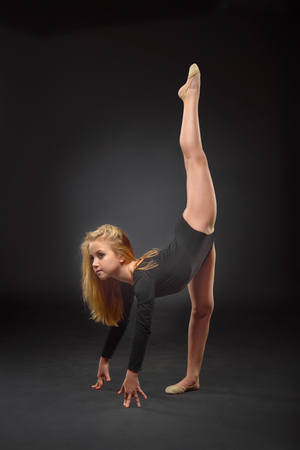 Childrens sports, athletics, rhythmic gymnastics concept - Young beautiful white caucasian girl gymnast with long hair doing gymnastic exercise on black background.