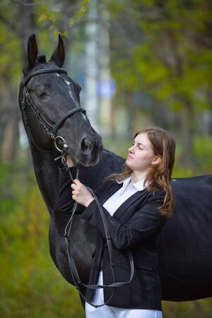 Young girl rider with a black horse in the spring