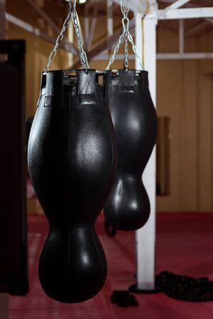 punching boxing bag in the sport gym. Sports, training, motivation, active lifestyle concept.