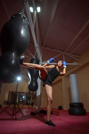 A young Caucasian woman actively trains in the gym and do boxing exercises in boxing gloves in front of a punching bag. Sports, training, motivation, active lifestyle concept.
