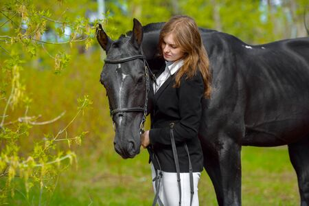Young girl rider with a black horse in the spring outdoors scene