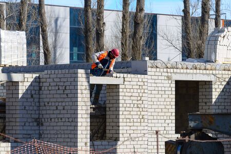 House construction. Construction of a new house. Workers erect the second floor of a building on a construction site. Reklamní fotografie