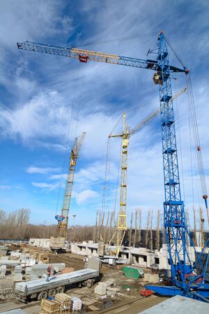 House construction. Top view of the construction site. Photos of high-rise construction cranes and an unfinished house against a blue sky. Crisis in the construction industry.