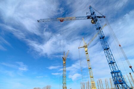 House construction. Photos of high-rise construction cranes and an unfinished house against a blue sky. Crisis in the construction industry. Photographed from the bottom up on a wide angle lens. Reklamní fotografie