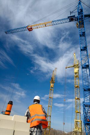 House construction. A worker in overalls looks at the high-rise construction cranes on the construction site against a blue sky. Crisis in the construction industry.