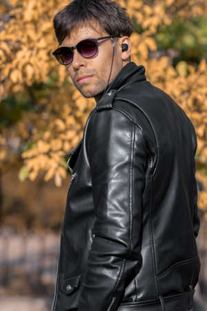 A guy in sunglasses and a leather jacket turns around looking over his shoulder
