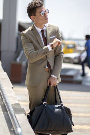 A man in a business suit and sunglasses, looks intensely at the watch on his hand, with his other hand holds his bag with luggage Imagens