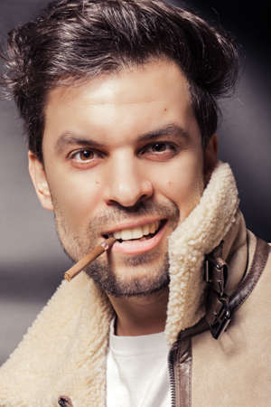 A man in a white sheepskin coat under a sheepskin holds a cigarette in his mouth and wants to laugh