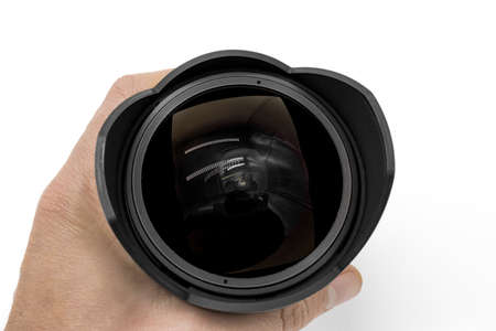 Hand holds black fisheye lens on white background Foto de archivo