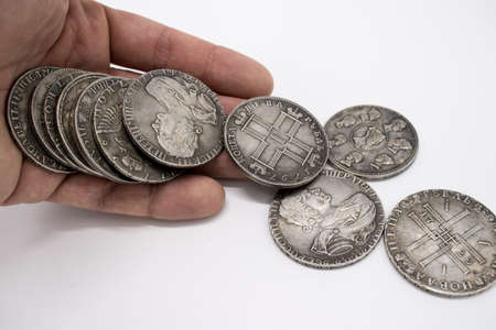 Old coins of tsarist Russia fall out of hand on white background