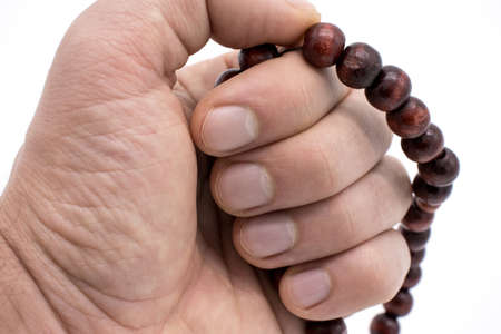 Hand holds wooden rosary on white background