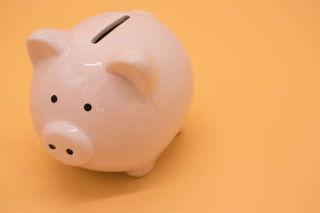 Pink piggy bank for money on yellow background