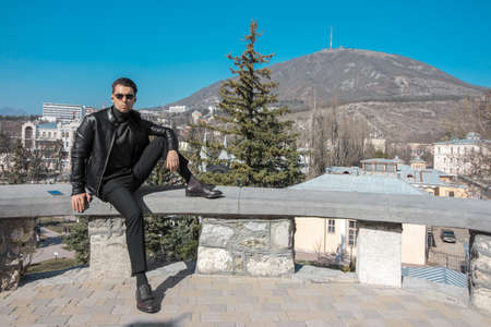 A man in black-style clothing sits on a concrete railing in the city of Pyatigorsk in the Stavropol Territory in a park called Flower Garden, in the distance you can see Mount Mashuk