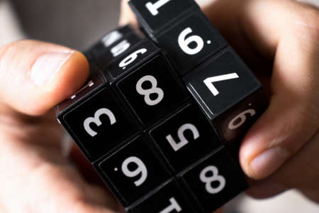 A man holds in his hands a black cube with numbers on its area for playing the Japanese game of Sudoku on a white background