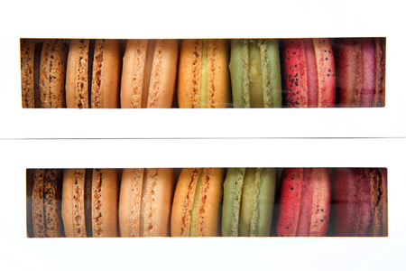 Macaron cookies in white boxes with clear plastic windows showing a display of colorful cookies. Stock Photo