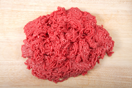 Close up of raw ground hamburger meat low fat, on a light wood cutting table