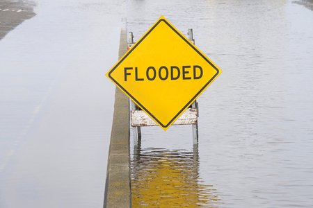Flooded sign in the middle of standing water in the road and on the adjacent parking area Imagens