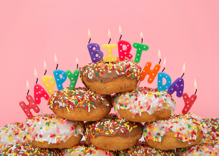 Chocolate and white frosted donuts covered in candy sprinkles piled into a cake pile with Happy Birthday candles burning brightly. Pink background.