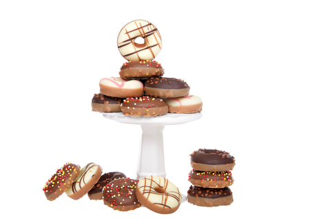 Many small donuts coated in candy and decorated with sprinkles stacked on a small pedestal with extras on the table, isolated on white.