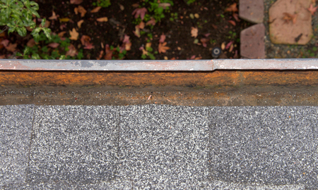 Close up on section of rain gutter on residential home, clean and uncovered. Debris like leaves, twigs can clog your gutter system, causing potential harm to your house, landscaping and the gutters.