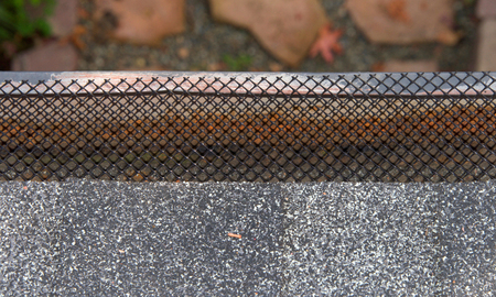 Close up on section of rain gutter on residential home, free of leaves and debri, covered with mesh. mesh helps to keep leaves and debri out of rain gutters to improve functionality and prevent damage
