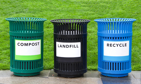 Variety of bright colorful trash cans in a park with grass in background. Green for Compost, black for landfill and blue recycling. copy space on labels for visual references to be added. 写真素材