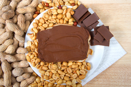 Chocolate peanutbutter spread on bread, open face sandwich on plate with pieces of chocolate, shelled peanuts and whole in shell peanuts on wood table. Tasty combination of chocolate and peanuts