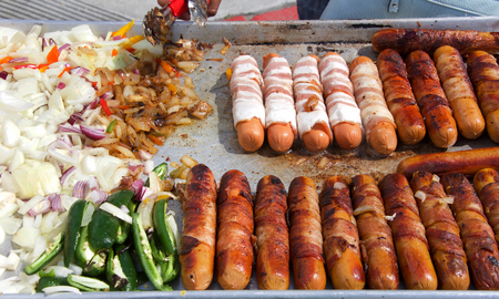 Street vendor cooking bacon wrapped hot dogs with onions and jalapeno peppers. Popular cuisine for street fairs and events Standard-Bild