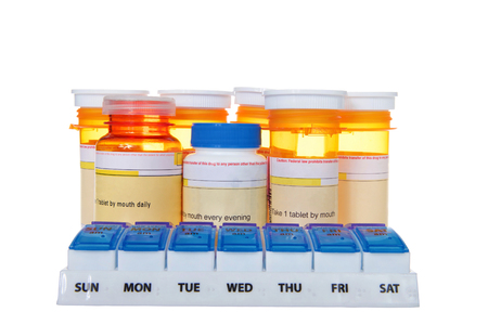 Twice daily medication organizer with many bottles of pills stacked behind it isolated on white background. Confusing to keep track of multiple meds. Braille on container for visually impaired. Stockfoto