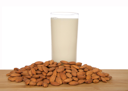 Glass of almond milk on a wood table surrounded by whole raw almonds, isolated on white background. Almond milk is lower in calories than other milks and cholesterol free, lactose free. 免版税图像
