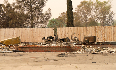 home burned to the ground, fence left untouched in the recent wild fire fire storm in Redding, California. Smoke and ash in the air as the fire continues to burn several miles away. Stock Photo